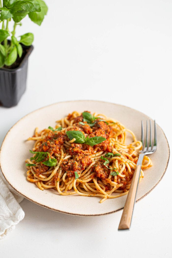 Plate of vegan spaghetti and bolognese sauce topped with basil and parmesan.