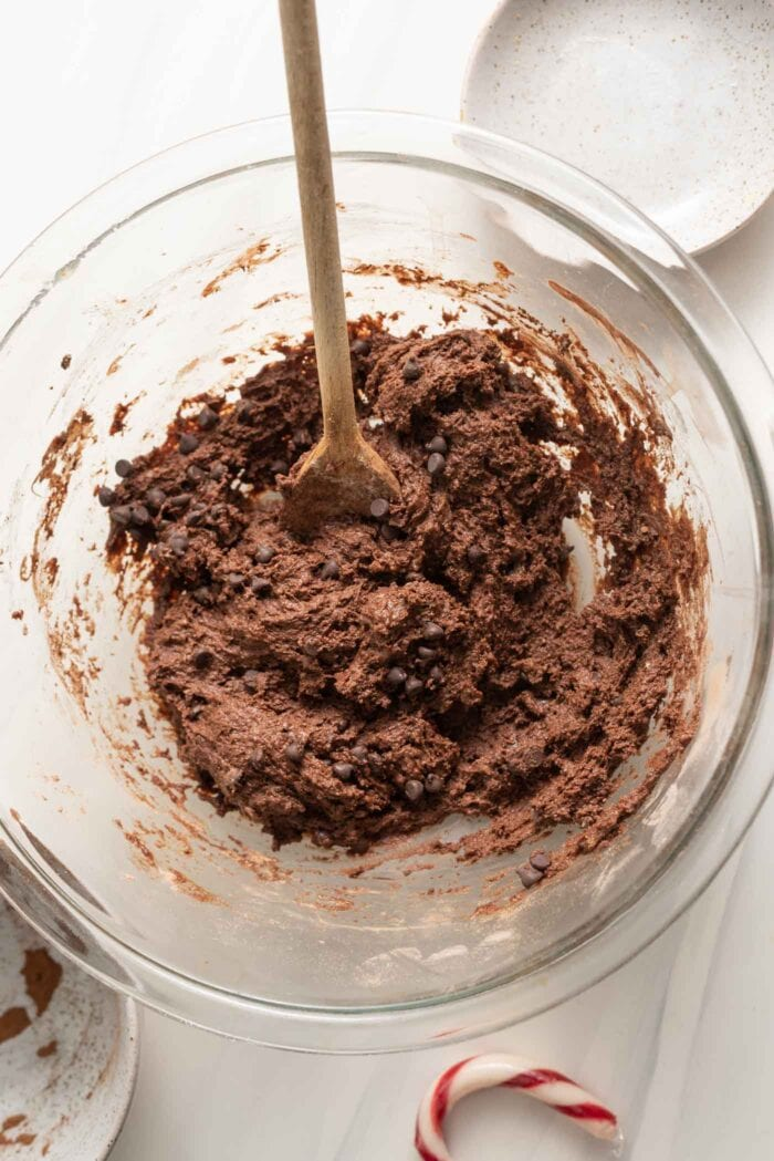 Chocolate batter with chocolate chips in it in a mixing bowl.
