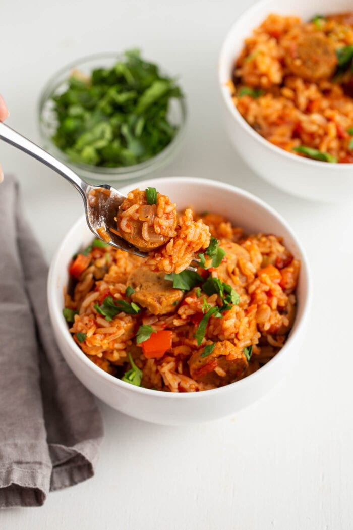 Forkful of jambalaya with a piece of sausage in it.