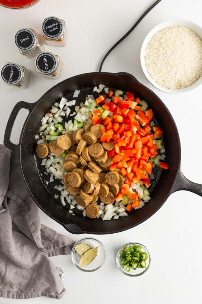 Sausage and bell peppers added to a skillet with onions, garlic and celery.