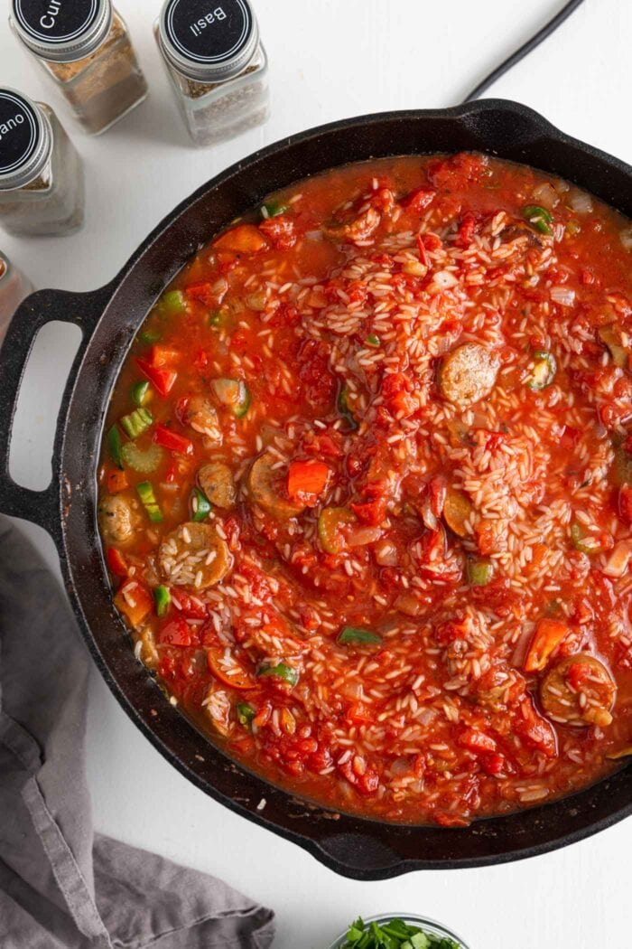Tomato sauce, rice and vegetables in a skillet.