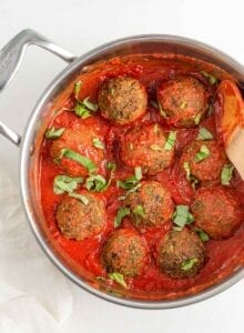 Overhead view of lentil meatballs in a skillet with sauce.