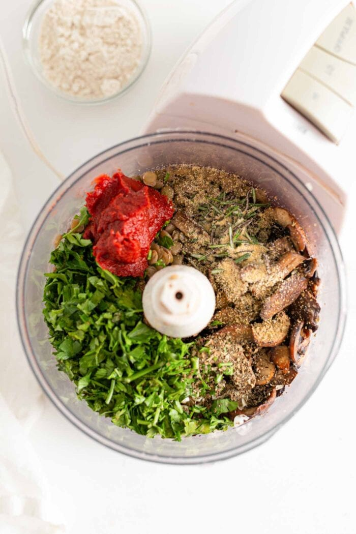 Chopped fresh herbs, tomato paste, lentils and mushrooms in a food processor.