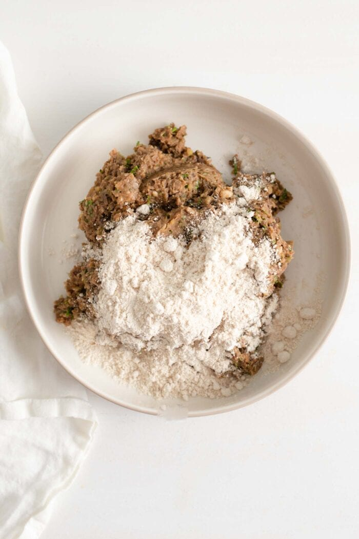 Ground lentil mixture with oat flour on top in a bowl.