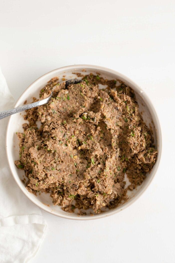 Ground lentil and mushroom mixture for making vegan meatballs in a bowl.