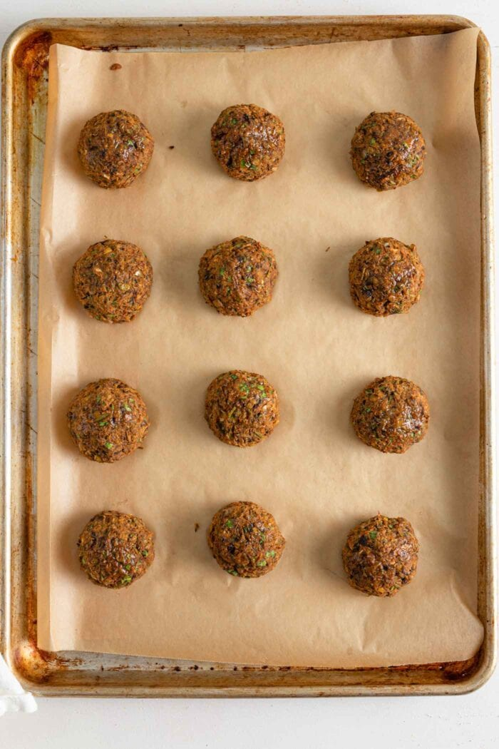 Baked lentil meatballs on a a baking tray.