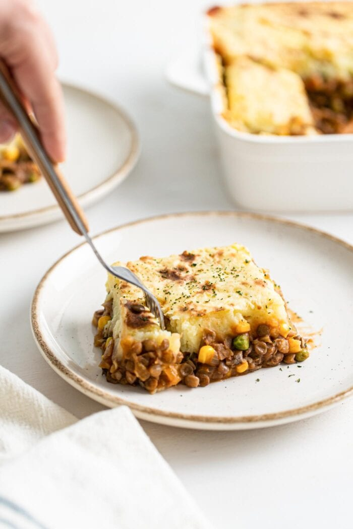 Fork taking a small portion out of a slice of lentil shepherd's pie.