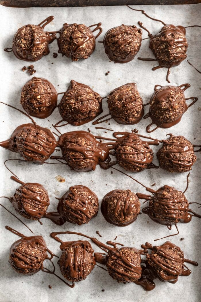 Baking tray of chocolate macaroons covered in drizzled melted chocolate.