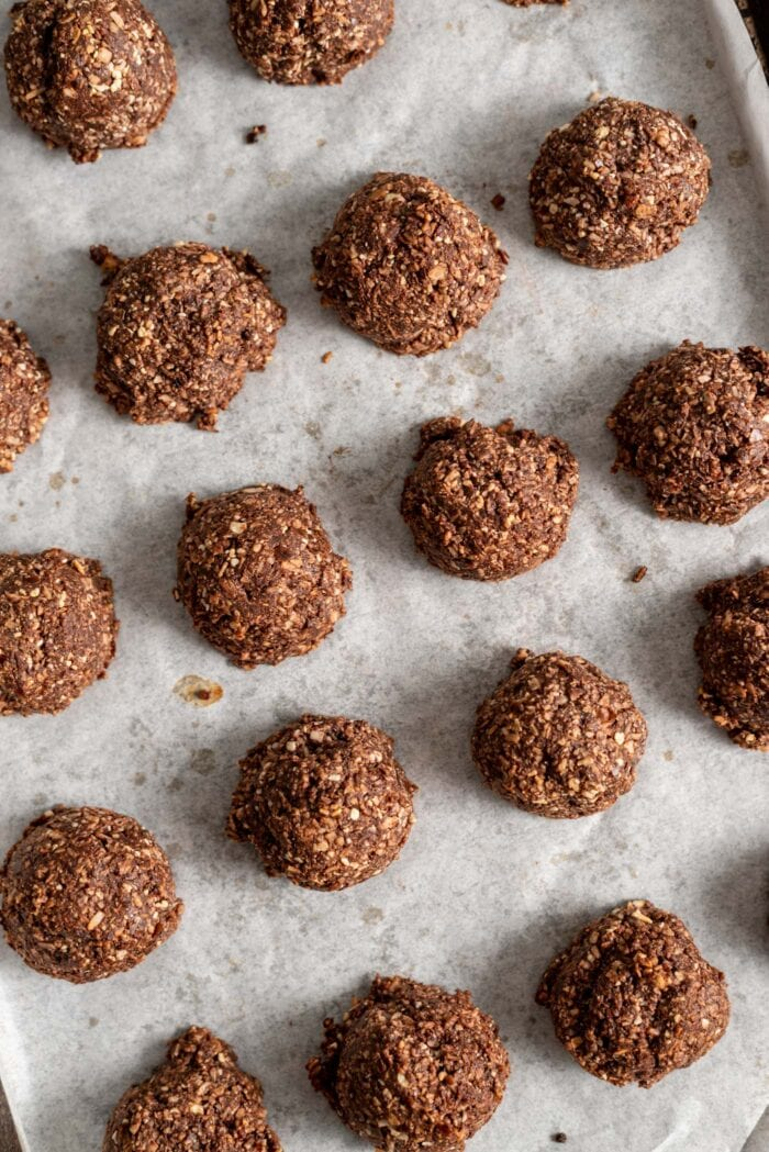 Baked chocolate macaroons on a parchment paper-lined baking tray.