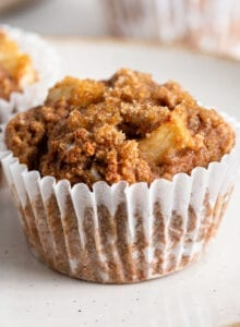 Two applesauce muffins on a plate. More muffins in background.