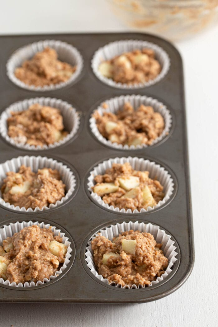 Raw muffin batter in a muffin liner-lined muffin tin.
