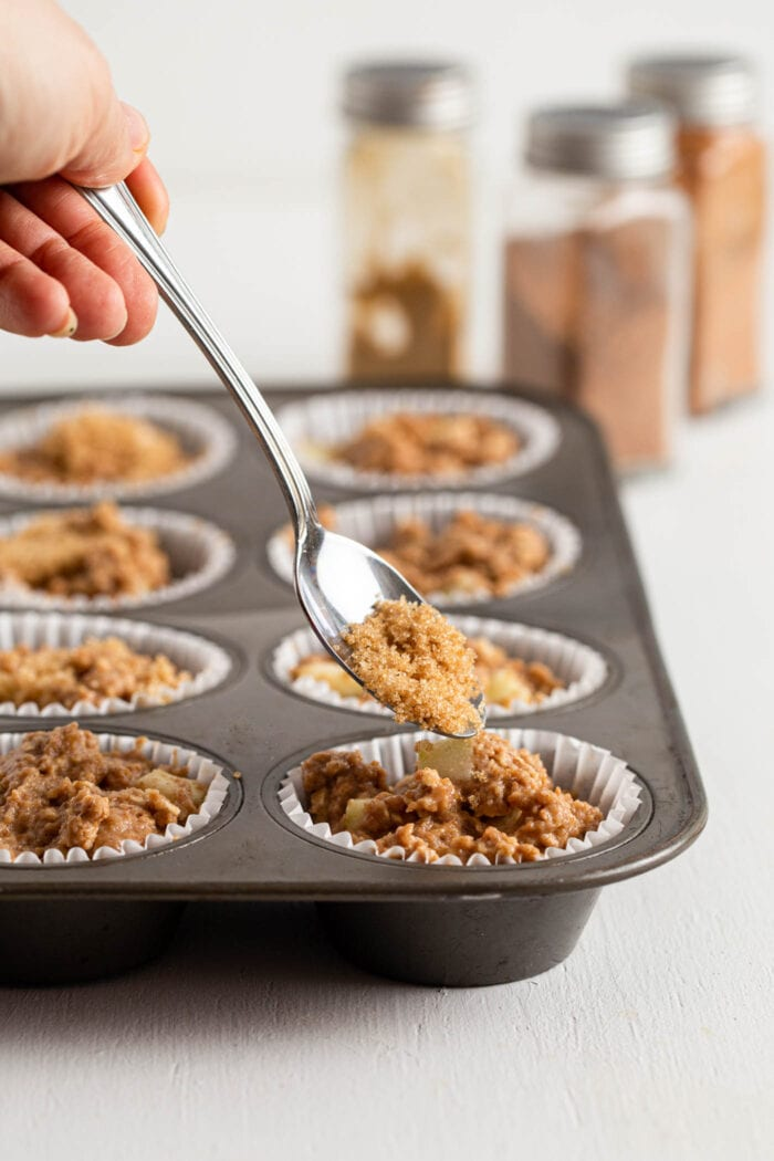 Spooning brown sugar onto a raw muffin in a muffin tin.