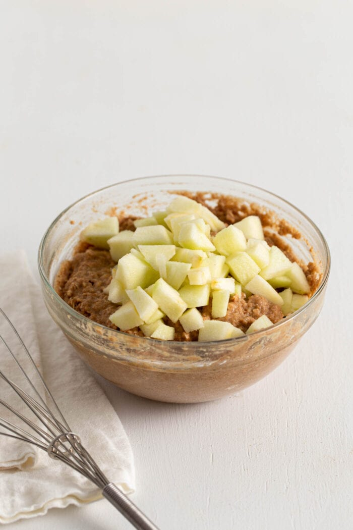 Bowl of raw muffin batter topped with diced apples.