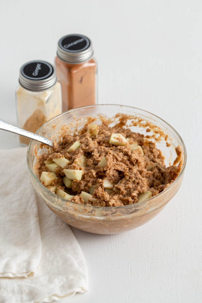 Muffin batter with diced apple mixed into it in a mixing bowl.