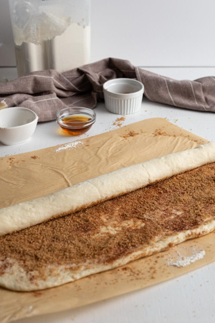Cinnamon roll dough being rolled into a tight log.