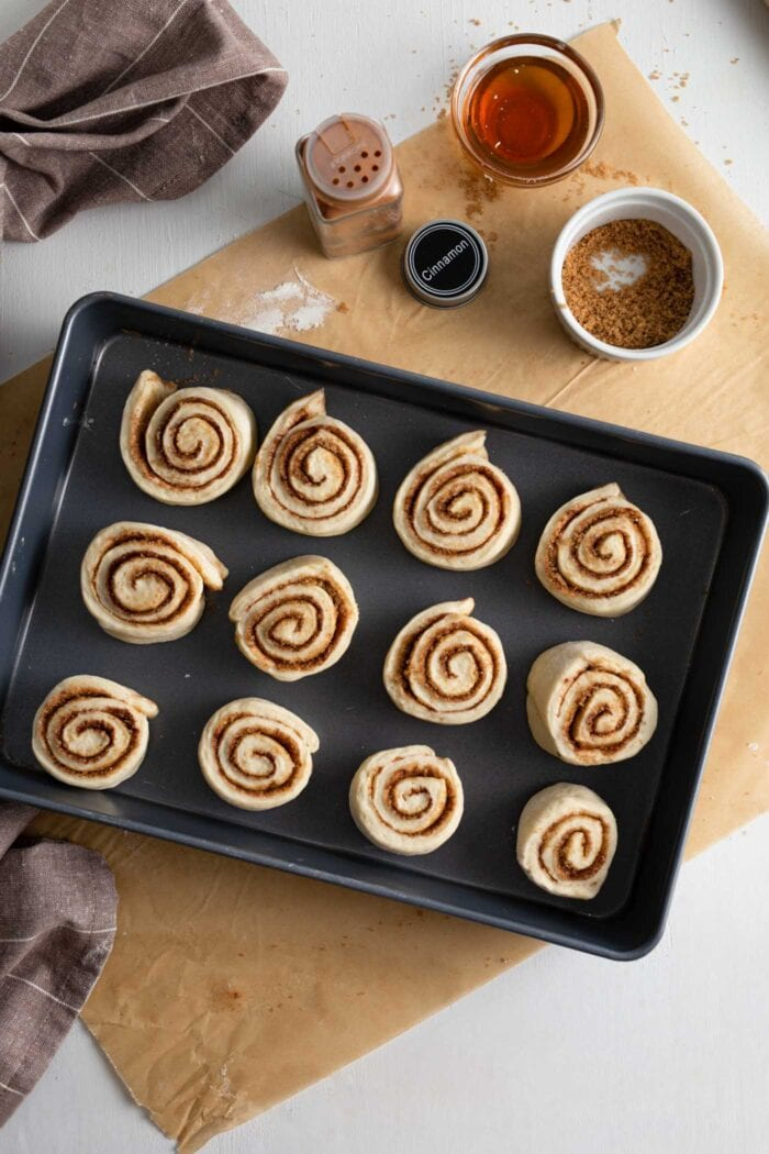 Raw cinnamon rolls in a baking pan.