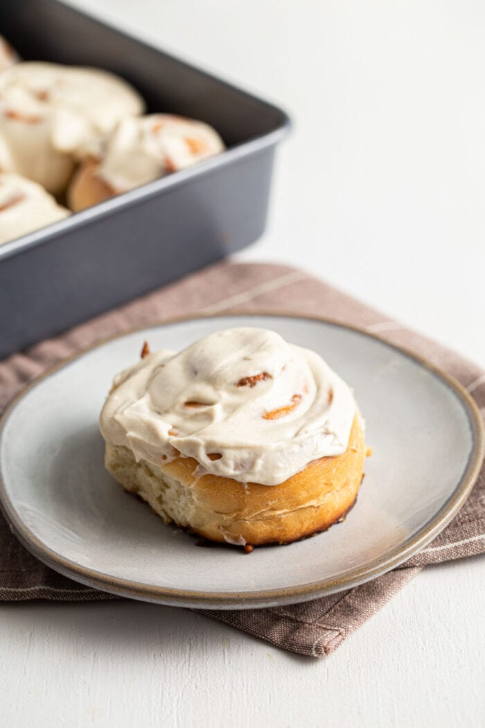 Vegan cinnamon bun topped with icing on a small plate.