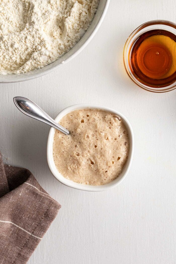Frothy yeast mixture in a small bowl with a spoon.