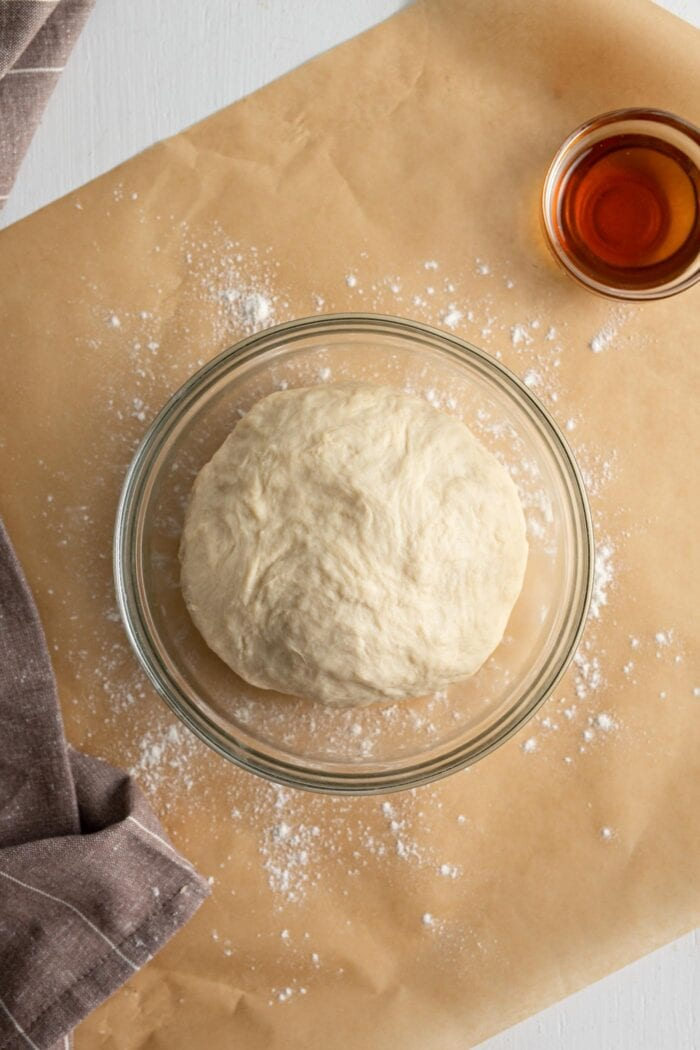 Cinnamon roll dough rolled into a ball and placed in a mixing bowl.