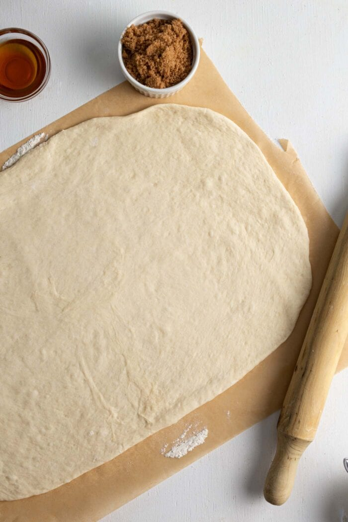 Cinnamon roll dough rolled into a large rectangle on a piece of parchment paper.