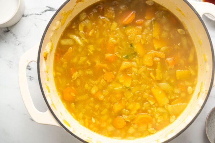 Squash, carrot and onion cooking in a curry broth in a large pot.