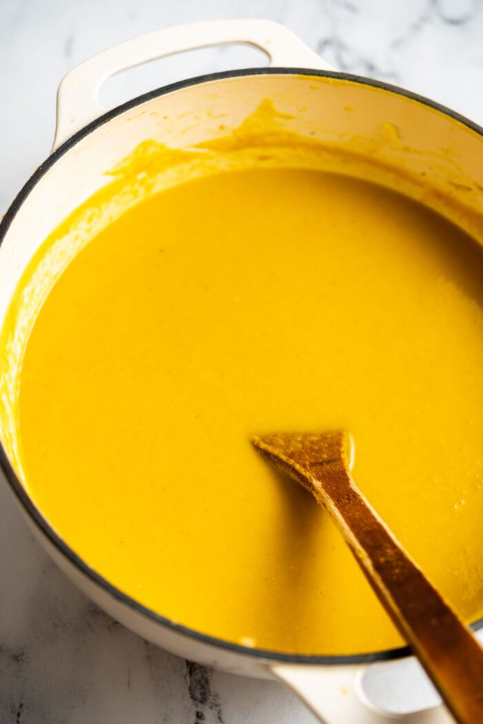 A large pot of creamy squash soup with a wooden spoon resting in the pot.