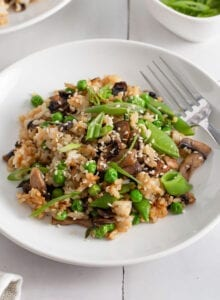 Mushroom fried rice topped with scallions and sesame seeds in a bowl.