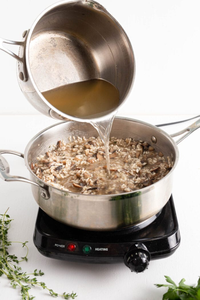 Pouring hot stock into a skillet of rice cooking on a small cooktop.