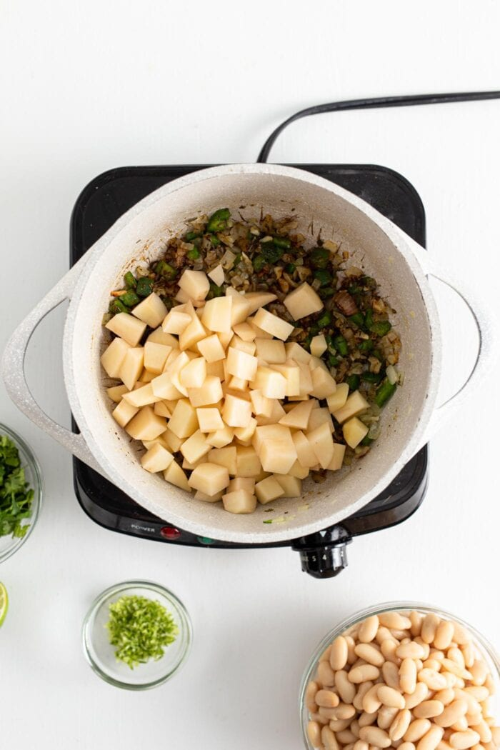 Jalapeno, diced potatoes, garlic and onion cooking in a large soup pot.