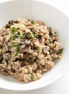 Close up of a bowl of vegan mushroom risotto topped with parsley.
