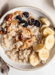 Overhead image of a bowl of oatmeal topped with peanut butter, banana and berries.