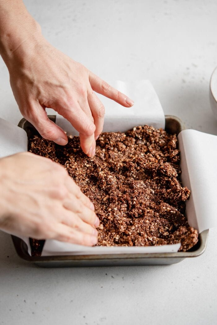 Hands pressing chocolate dough into a parchment paper-lined baking tray.