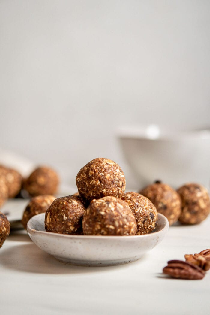 A few raw banana bread energy balls in a small dish. More balls in background.