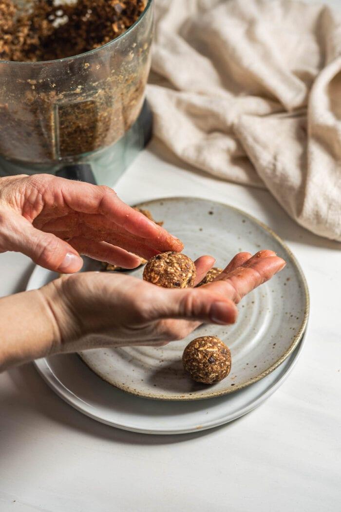 Hands rolling energy ball dough into balls.