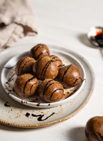 Gingerbread energy balls drizzled with molasses on a small plate.