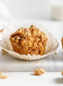 Small carrot muffin in a cupcake liner sitting on a marble cutting board.