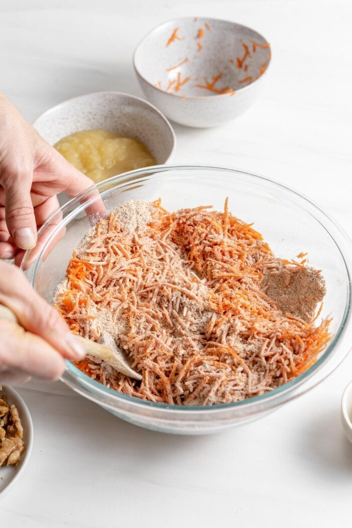 Mixing grated carrots into flour in a large mixing bowl.