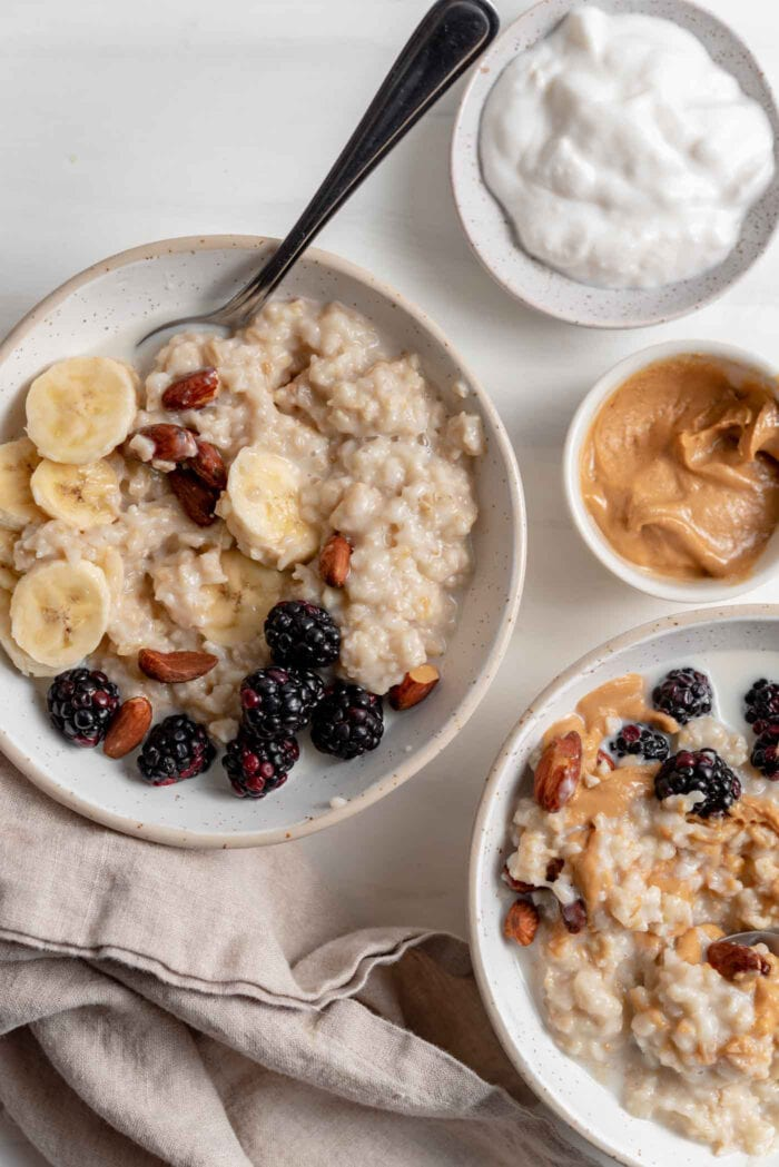 Two bowls of oatmeal topped with berries, banana and peanut butter.