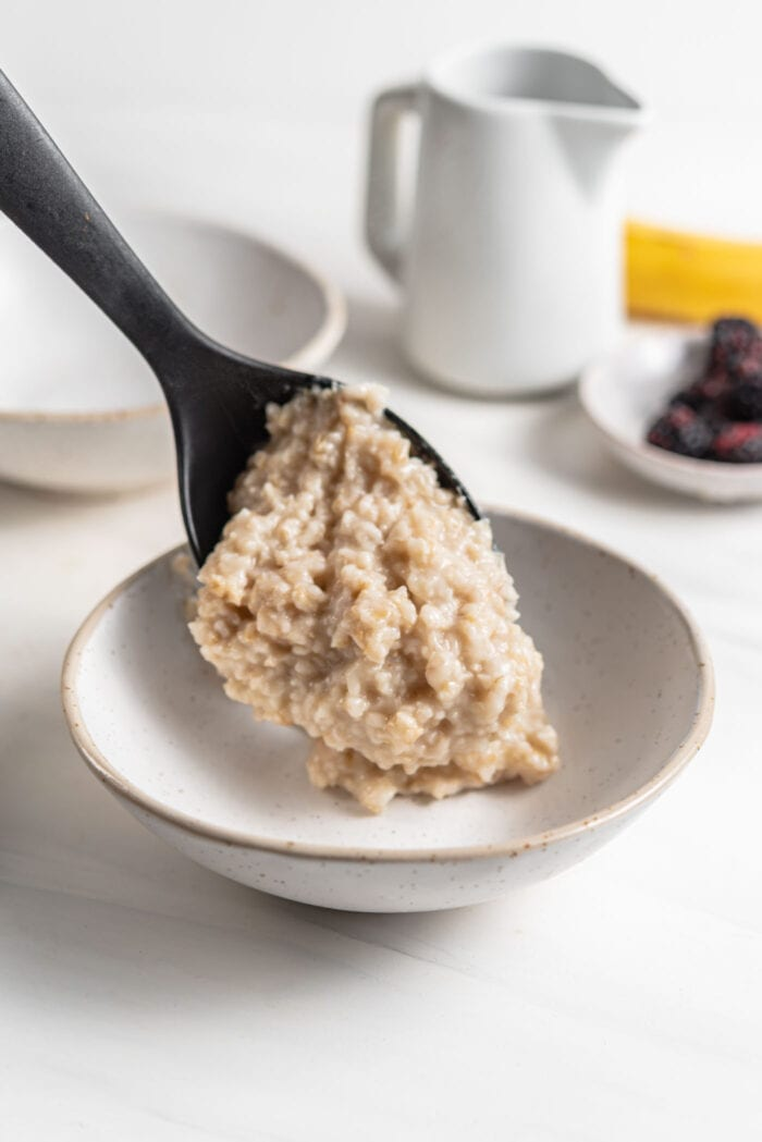 Adding a large scoop of cooked oatmeal to a bowl.