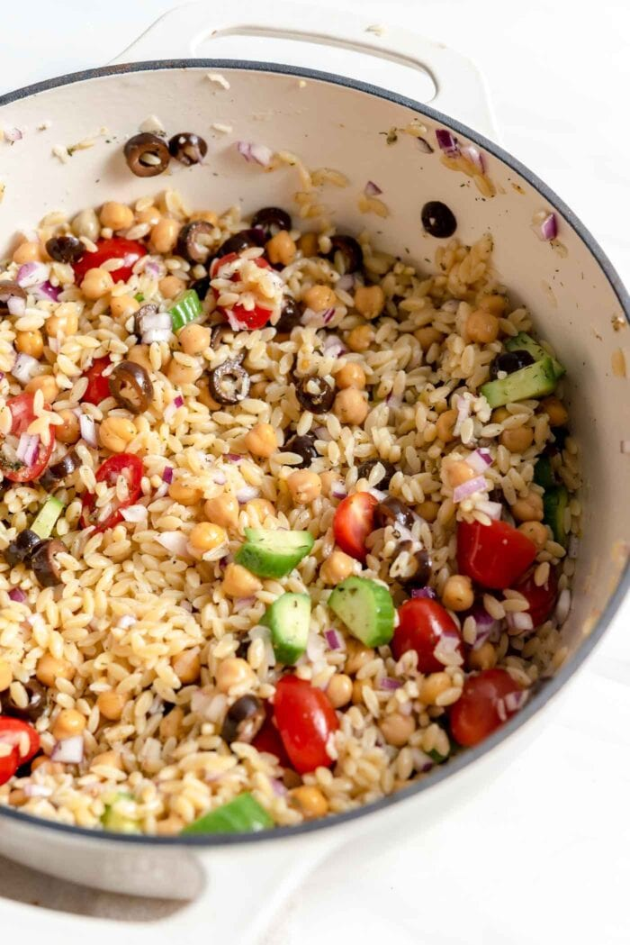 Mixed Mediterranean-style orzo salad with chickpeas and vegetables in a large pot.