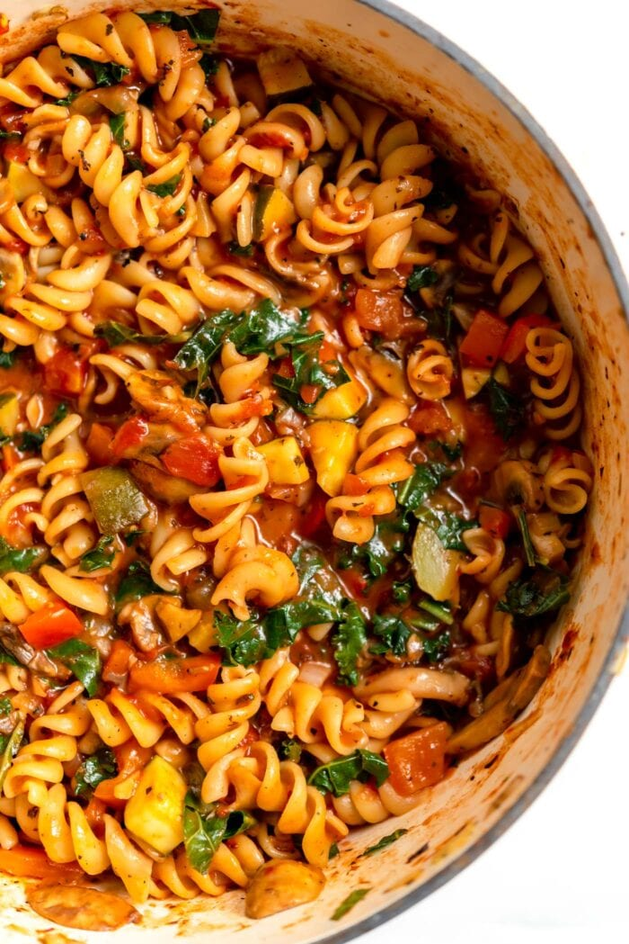 Overhead view of a large pot of rotini pasta and vegetables in tomato sauce.