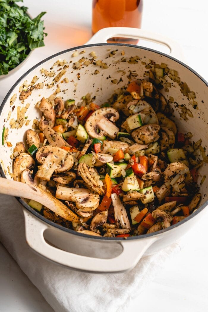 Chopped mushrooms, bell peppers and zucchini cooking in a large pot.