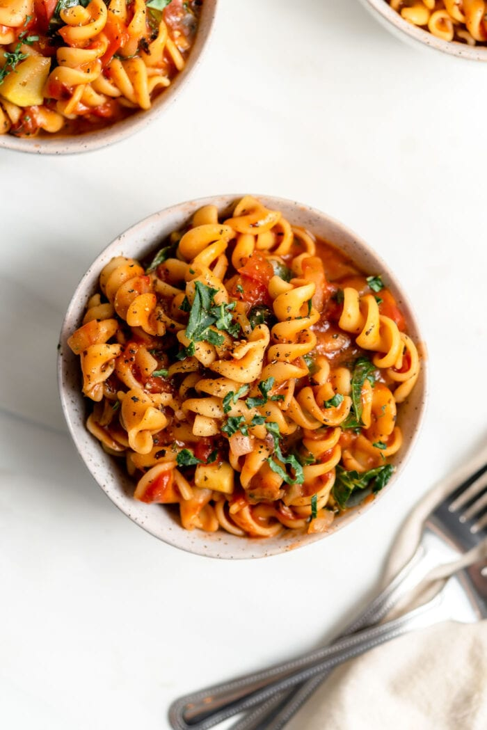 Overhead view of a bowl of rotini pasta with tomato sauce and vegetables.