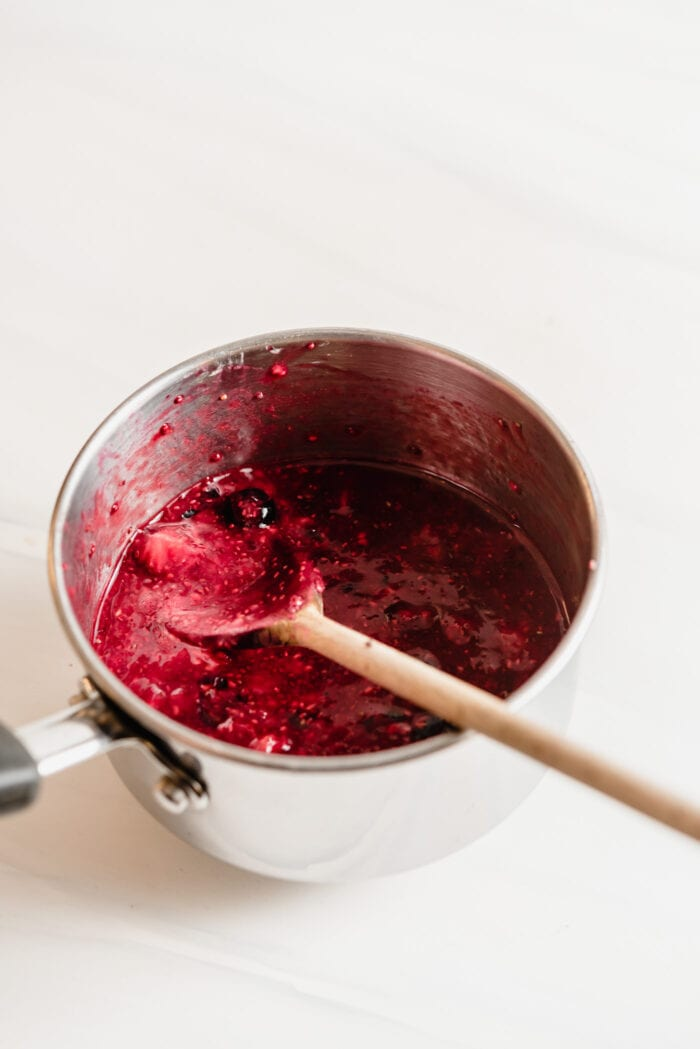 Mashing cooked berries up in a small pot.