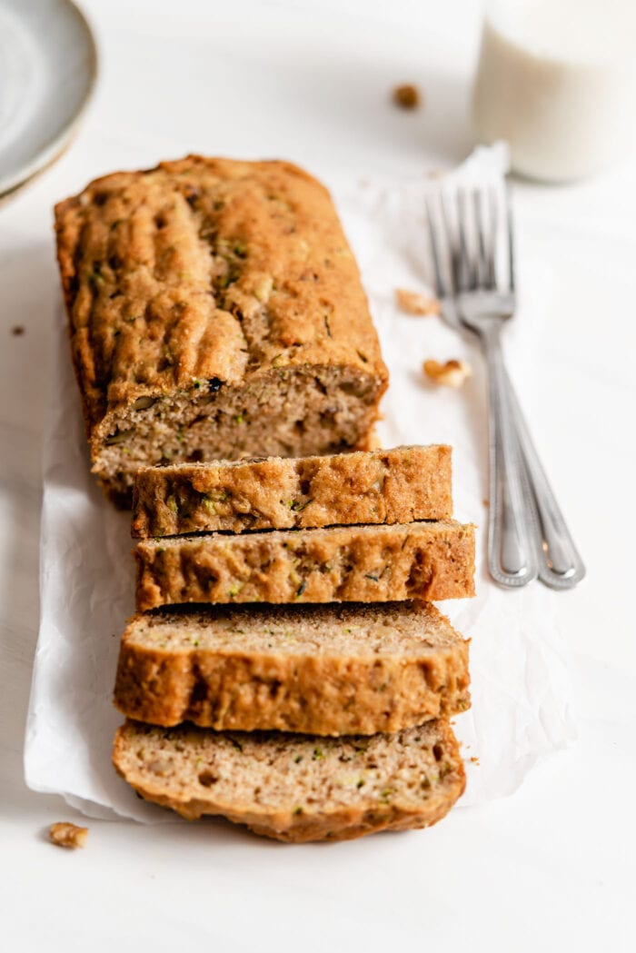 Vegan zucchini bread loaf sliced into 5 pieces on a piece of parchment paper. 2 forks rest beside loaf.