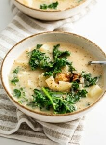 Two bowls of vegan zuppa toscana soup with potato and kale. Spoon rests in bowl.