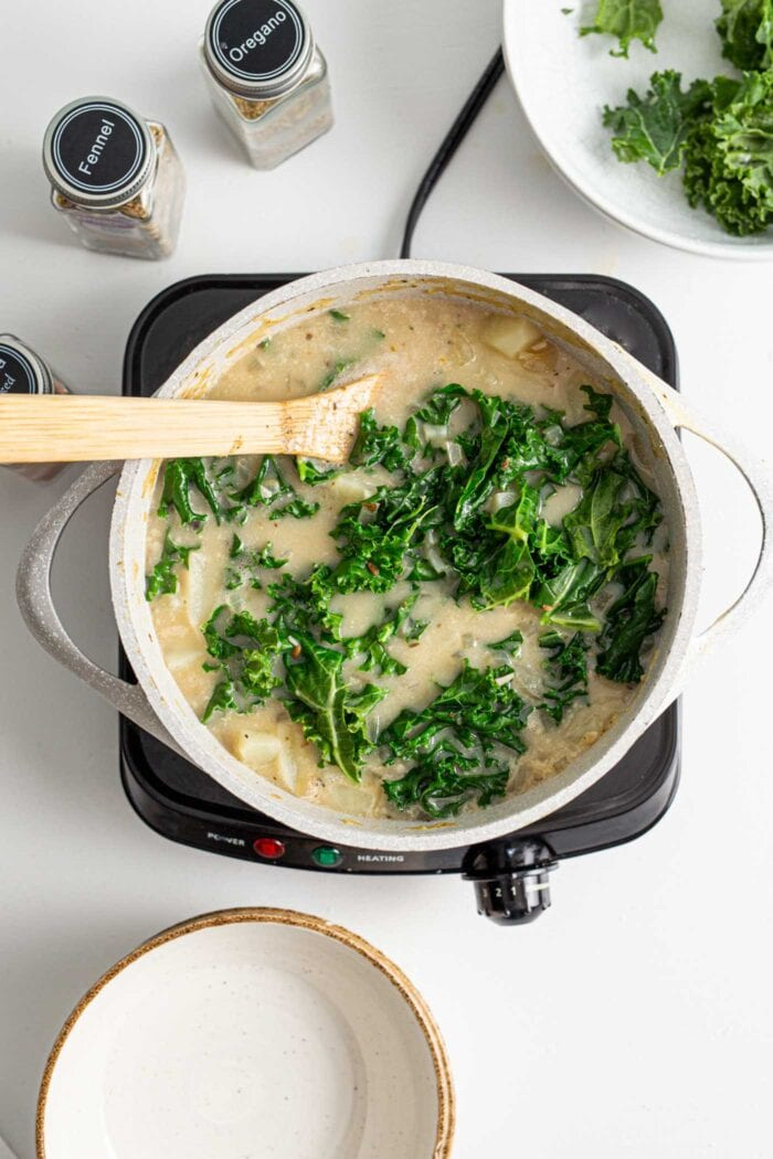 Overhead view of a pot of zuppa toscana soup with kale.