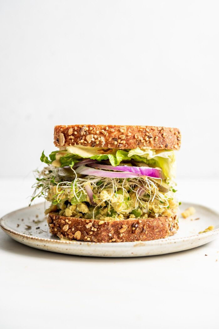 Front view of a chickpea salad sandwich with sprouts, pickles and red onion on it.