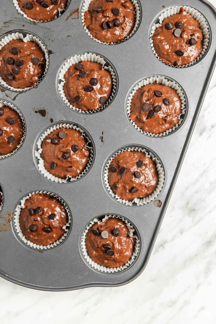 Raw chocolate chip muffin batter in a cupcake liner-lined muffin pan.