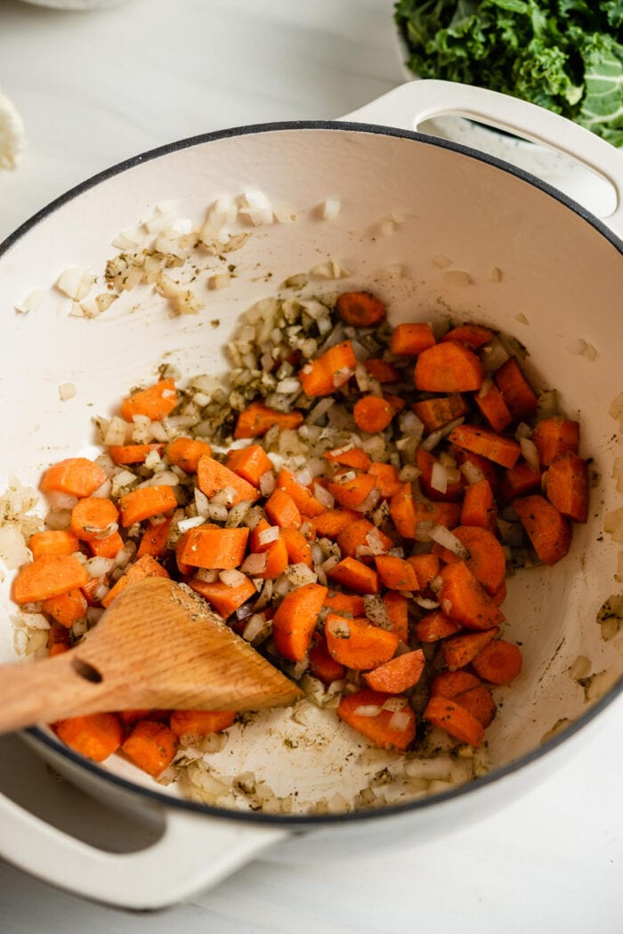 Chopped carrots, onion and garlic cooking in a large soup pot.